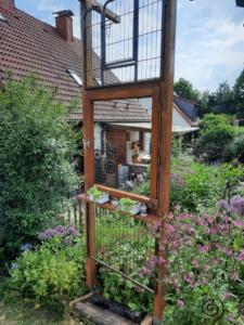 Holzfenster mit Gitter ober- und unterhalb und Blumentöpfe auf der Fensterbank
